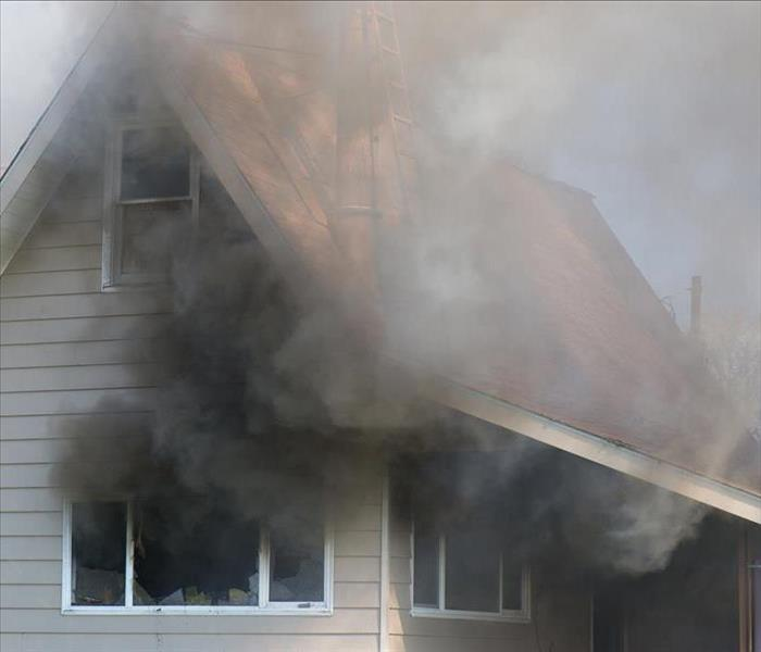 Image of a house with fire and smoke damage on the exterior.