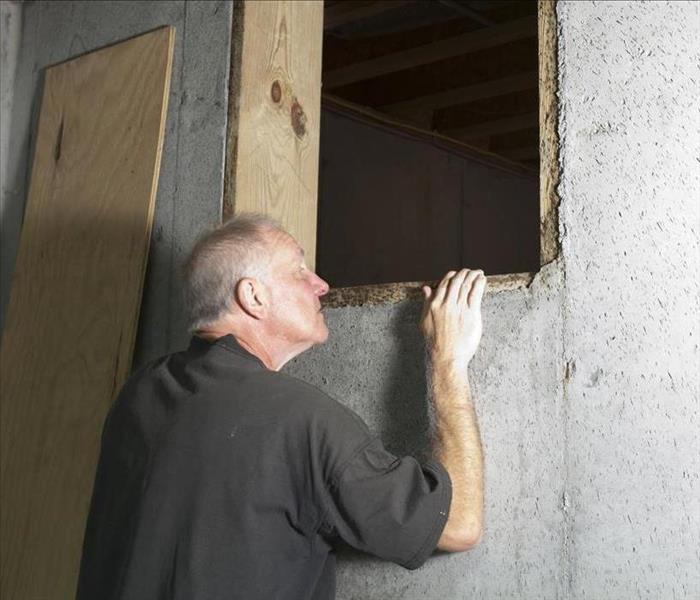 Image of a person looking into a crawlspace