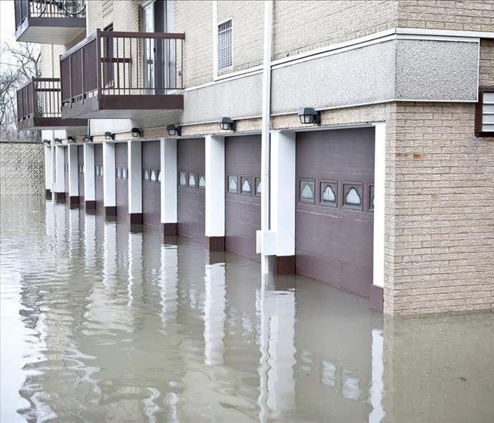 Image of a street flooded causing damage to near by buildings.